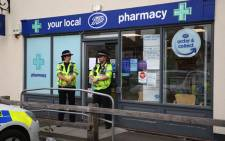 Police officers are seen standing guard outside a local pharmacy in Amesbury, nine miles north of Salisbury, southern England, on 4 July 2018 where two people were found unconscious at a residence in Amesbury in circumstances that caused a major incident to be declared were believed to have visited. Picture: AFP.