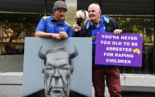 Protesters hold placards outside the County Court to hear the sentencing of Cardinal George Pell in Melbourne on 13 March 2019. Picture: AFP