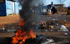Women collect water behind burning tyres during a service delivery protest in Thokoza on 28 July, 2009. Picture: Taurai Maduna/Eyewitness News
