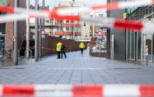 A picture taken on 1 January 2019 in Bottrop, Berlin, shows policemen standing in a cordoned off area at the site where a man injured four people after driving into a group celebrating the new year, in what police described as an anti-migrant attack. Picture: AFP.