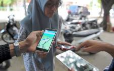 This picture taken on 16 July 2016 shows a group of Indonesians playing Pokémon Go on the streets in Banda Aceh. Picture: AFP.