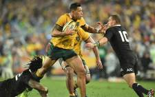 Australian Wallabies fullback Israel Folau (C) pushes away New Zealand All Blacks fly-half Aaron Cruden (R) during their rugby union Test match in Sydney on 16 August, 2014. Picture: AFP.