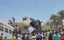 A video grab taken from the Egyptian state television station shows people gathered around two trains that collided in the Tahta district of Sohag province, some 460 kms (285 miles) south of the Egyptian capital Cairo, reportedly killing at least 32 people and injuring scores of others, on 26 March 2021. Picture: Egyptian State TV/AFP