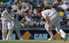 Australian bowler Peter Siddle attempts to stop a shot from South Africa's Dean Elgar (L). Picture: AFP.