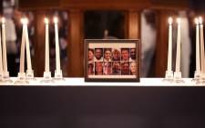A photograph of the victims of a mass shooting is surrounded by 12 candles during a memorial service at Piney Grove Baptist Church 2 June 2019 in Virginia Beach, Virginia. Picture: AFP