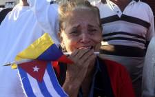 A woman cries as the urn with the ashes of Cuban leader Fidel Castro is driven through the streets of Havana. Picture: AFP.
