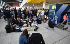 Passengers wait at the North Terminal at London Gatwick Airport, south of London, on 20 December 2018 after all flights were grounded due to drones flying over the airfield. London Gatwick Airport was forced to suspend all flights on December 20 due to drones flying over the airfield, causing misery for tens of thousands of stuck passengers just days before Christmas. Picture: AFP.