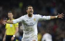 Real Madrids Portuguese forward Cristiano Ronaldo celebrates after scoring his third goal during the Champions League quarter-final second leg football match Real Madrid vs Wolfsburg at the Santiago Bernabeu stadium in Madrid on 12 April, 2016. Picture: AFP.