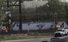 Maintenance workers move a train car from the wreckage of an Amtrak Northeast Regional Train in Philadelphia, Pennsylvania, on 13 May, 2015. Picture: AFP.