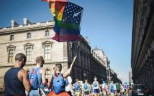 A man waves the rainbow flag as he takes part with others participants in the Rainbow Run, from Paris City Hall to Place de la Concorde during the opening day of the 2018 Gay Games' edition, in Paris, on August 4, 2018. Picture: AFP.