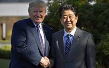 US President Donald Trump (L) shakes hands with Japanese Prime Minister Shinzo Abe upon his arrival at the Kasumigaseki Country Club in Kawagoe, near Tokyo on 5 November 2017. Picture: AFP.