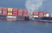 In this photo released by the Canadian Coast Guard and received by AFP on 24 October 2021, smoke is seen rising from the side of the container ship Zim Kingston off Canada's Pacific coast. Picture: AFP