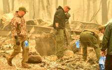 Yuba and Butte County Sheriff officers react as they discover a body at a burned out residence after the camp fire tore through the area in Paradise, California on 10 November 2018. Picture: AFP
