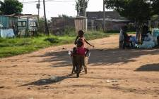Children play with a wheelbarrow in Ebumnandini on the West Rand after dumping waste at a dumpsite nearby. Picture: Kayleen Morgan/EWN