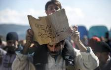 "A man carries on his shoulders a child holding a banner reading ""Open the borders"" during a demostration of migrants and refugees protesting behind a fence and barbed wire at the Greek-Macedonian border, near Gevgelija, on February 27, 2016. Picture: AFP."