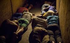 FILE: Men lie flat on the floor while police search their rooms for illegal weapons, stolen goods and drugs during an overnight raid at the Jeppestown hostel on 21 April 2015. Picture: Thomas Holder/EWN.
