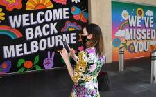 A woman stands in front of posters after measures to curb the spread of the COVID-19 coronavirus were eased allowing limited numbers of people back into shops, bars, cafes, and restaurants in Melbourne on 28 October 2020. Picture: AFP