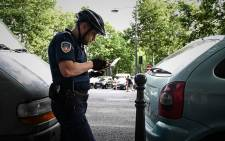 An officer of the Paris city prevention and security direction (DPSP) checks a car plate during a pollution control operation on private vehicles in Paris on 1 July 2019. Picture: AFP