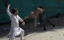 Afghan protesters beat a policeman after a suicide attack that targeted crowds of minority Shiite Hazaras during a demonstration at the Deh Mazang Circle of Kabul on 23 July 2016. Picture: Wakil Kohsar/AFP.
