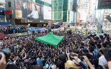A crowd of pro-democracy protesters and journalists watch workers remove a tent in a blocked section of Argyle Street in Mongkok, Hong Kong, China, 25 November 2014. Picture: EPA.