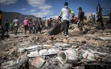 Residents of the Imizamo Yethu informal settlement in Hout Bay, Cape Town, help to clear the rubble on 28 December 2015 after a fire ripped through a section. Picture: Aletta Harrison/EWN.