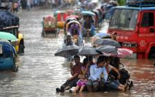 Bangladeshi pedestrians holding umbrellas hitch a ride on a rickshaw van as they attempt to stay dry over flood waters in the Bangladeshi capital of Dhaka on July 28, 2009. Picture: AFP