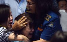 Family members of passengers onboard the missing Malaysian air carrier AirAsia flight QZ8501 react after watching news reports showing an unidentified body floating in the Java sea, inside the crisis-centre set up at Juanda International Airport in Surabaya on December 30, 2014. Picture: AFP.