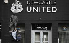 A Newcastle United supporter is seen posing in front of the statue of the late former manager Bobby Robson outside the club's stadium St James' Park in Newcastle upon Tyne in northeast England on 8 October 2021, after the sale of the football club to a Saudi-led consortium was confirmed the previous day. Picture: Oli Scarff/AFP