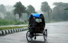 This file photo shows a rickshaw rides through heavy rain in Berhampur, India. Picture: AFP