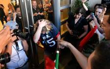 A woman wearing a Trump shirt (C) is pelted with eggs by protesters while pinned against a door near where Republican presidential candidate Donald Trump holds a rally in San Jose, California on 2 June  2016. Protesters attacked Trump supporters as they left the rally, burned an American flag, trump paraphernalia and scuffled with police and each other. Picture: AFP/JOSH EDELSON