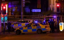 """Police deploy at scene of explosion in Manchester, England, on 23 May 2017 at a concert. British police said early 23 May there were """"a number of confirmed fatalities"""" after reports of at least one explosion during a pop concert by US singer Ariana Grande. Picture: AFP."""