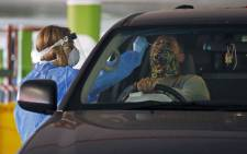 FILE: FILE: A Dis-Chem Pharmacy health professional collects a nasal swab for a COVID-19 coronavirus test at a drive-through testing site. Picture: AFP