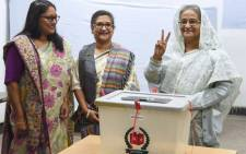 FILE: Bangladeshi Prime Minister Sheikh Hasina (R) flashes the victory symbol after casting her vote, as her daughter Saima Wazed Hossain and her sister Sheikh Rehana look on at a polling station in Dhaka on 30 December 2018. Picture: AFP