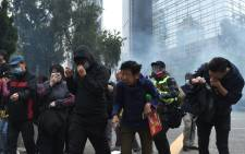 eople react from tear gas fired by police to disperse the crowd gathered for the 'universal siege on communists' rally at Chater Garden in Hong Kong on 19 January 2020. Picture: AFP