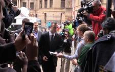 Oscar Pistorius receives a bible from a supporter as he enters the High Court in Pretoria ahead of his murder trial on 17 April 2014. Picture: Christa van der Walt/EWN