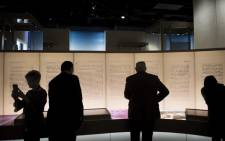 In this file photo taken on 14 November 2017, visitors look at an exhibit about the Dead Sea scrolls, which are in fact fake, and will no longer be displayed. Picture: AFP