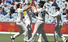 Australia's Pat Cummins (L) celebrates with teammates after dismissing India's captain Virat Kohli as India is all out for only 36 runs on the third day of the first cricket Test match between Australia and India played in Adelaide on 19 December 2020. Picture: AFP