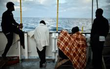 In this file photo taken on 14 May 2018 migrants look at the coastline as they stand aboard rescue ship MV Aquarius, off the coast of Sicily. Picture: AFP