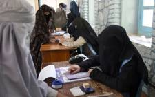An Afghan Independent Election Commission (IEC) official (R) prepares ballot papers for voters at a polling centre for the country's legislative election in Kandahar province on 27 October 2018. Picture: AFP