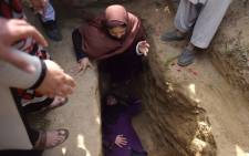 Independent Afghan civil society activist women weep and lie on the grave of Afghan woman Farkhunda, 27, who was lynched by an angry mob, at the cemetary in central Kabul on March 22, 2015.