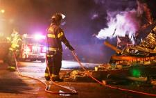 FILE: Firefighters work to put out a fire at a business after protesters burned buildings in protest against the Grand Jury decision not to indict a white police officer in the shooting of black male, Michael Brown, in Ferguson, Missouri. Picture: EPA.