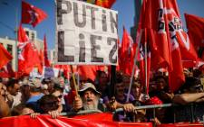 Russian Communist party supporters and country's left-wing movements carry red flags as they take part in a rally against the government's proposed reform hiking the pension age in Moscow on 2 September 2018. Picture: AFP.