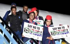 Air Peace flight attendants hold placards to denounce xenophobia as the first group of Nigerians repatriated from South Africa following xenophobic violence arrives in Lagos, on 11 September 2019. Picture: AFP
