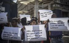 A group of protesters of the #NoToVaccination group gather outside the University of the Witwatersrand in Johannesburg, on 1 July 2020 for a protest against the coronavirus vaccine trials in Africa. Picture: AFP