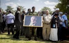 An SANDF member stands with a portrait of struggle stalwart Ahmed Kathrada is carried with the procession as his coffin is taking to the grave at West Park cemetery in Johannesburg on 29 March 2017. Picture: Reinart Toerien/EWN