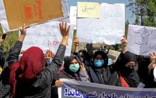 Afghan women hold placards as they take part in a rare protest in Herat on 2 September 2021. Picture: AFP