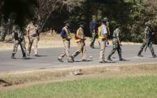 FILE: Armed Malawian policemen walk on a road as they disperse supporters of The Malawi Congress Party (MCP) in Lilongwe on 6 June 2019, as they attempt to prevent them from regrouping on the second day of their protest against recently President Peter Mutharika's ascension to power. Picture: AFP