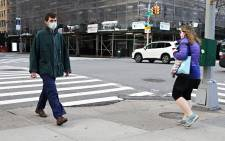 FILE: Two people wearing protective masks pass on the street during the COVID-19 pandemic on 21 April 2020 in New York City. COVID-19 has spread to most countries around the world, claiming over 175,000 lives with infections over 2.5 million people. Picture: AFP.