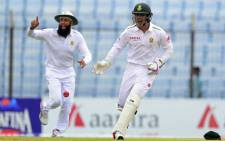 Quinton de Kock and Hashim Amla celebrate the fall of a wicket in Chittagong, Bangladesh on 22 July 2015. Picture: AFP.