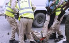 FIEL: Somali police officers carry the body of a fellow officer in Mogadishu. Picture: AFP